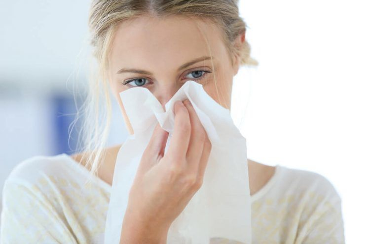Young-woman-with-cold-blowing-her-runny-nose-e1462599578651.jpg